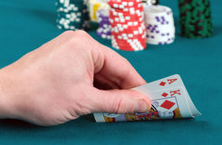 Table for poker. The player slightly opens cards, an as of diamonds and the king Stock Photography