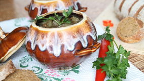 On the table is a pot of soup. The dish is decorated with a sprig of greenery. stock video footage