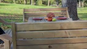 Table prepared for tow in the urban location. Low to high close up footage of a wooden table and chars prepared for two in the beautiful urban scenery on the stock footage