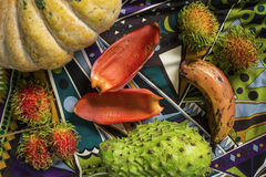 Table with pumpkin, rambutans, soursup and red banana. Still life composition with tropical fruits and vegetables. Royalty Free Stock Image