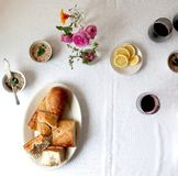 Table with ramekins of seafood pate, lemons, wine, and a platter of sliced baguette, from above stock photo