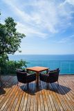 Table and rattan outdoor armchair setting on wooden deck and glass balcony with panoramic Andaman ocean sea view, green tree stock photo