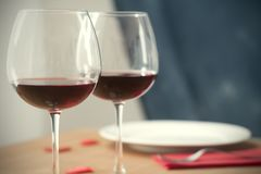 Dinner table with two wine glassis a plate and a fork. Table ready for a romantic dinner with wine glasses a plate an a fork on a napkin: valentine day or stock images