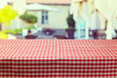 Table with red checked tablecloth over blur restaurant background. Ready for product montage Stock Image