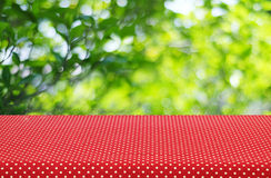 Table with red polka dot tablecloth and blur trees with bokeh ba Royalty Free Stock Photography