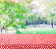 Table with red tablecloth and blur trees with bokeh background. Product display montage Royalty Free Stock Images