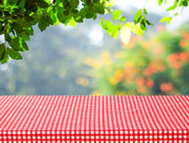 Table with red tablecloth and blur trees with bokeh background Royalty Free Stock Photo