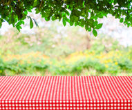 Table with red tablecloth and blur trees with bokeh background Stock Photo