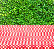Table with red tablecloth and trees background Royalty Free Stock Images