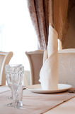 Table in restaurant with napkin, decor. Beige. Stock Photo