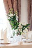 Table in restaurant with napkin, decor. Beige. Lily Stock Photo
