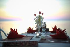 Table in the restaurant on the sea background decorated of flowers. Table is ready for Dinner at the Beach royalty free stock photos