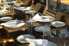Table in restaurant served for several people with dark chairs, Stock Photo