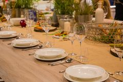 Table in the restaurant served for several persons with glasses and plates Stock Image