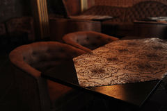 The table in the restaurant. Subdued dark lighting. Velour cloth Stock Images