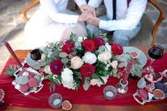 Table romantique avec les fleurs fraîches et bougies avec des couples dans l'amour sur le fond Images libres de droits
