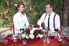 Table romantique avec les fleurs fraîches et bougies avec des couples dans l'amour sur le fond Images stock
