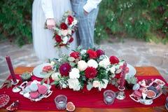 Table romantique avec les fleurs fraîches et bougies avec des couples dans l'amour sur le fond Photo libre de droits