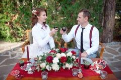 Table romantique avec les fleurs fraîches et bougies avec des couples dans l'amour sur le fond Photo stock