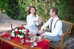 Table romantique avec les fleurs fraîches et bougies avec des couples dans l'amour sur le fond Photographie stock