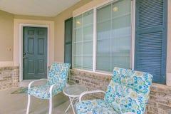 Table ronde et chaises colorées devant la fenêtre au porche d'une maison image stock