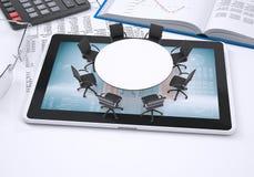 Table ronde, PC de comprimé, livre, calculatrice, verres Photo libre de droits