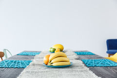 Table in room. Wooden colorful decorated table with fruit in white room Royalty Free Stock Photography