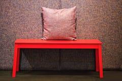 Table rouge avec l'oreiller rouge sur l'éclairage de dimm Photo libre de droits