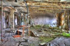Table rouillée et chaise abandonnée dans la salle de pension photos libres de droits