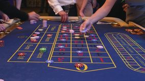 A table with a roulette in a casino. The croupier gives out a prize. Gambling for money. People make bets on roulette. Underground Casino stock video
