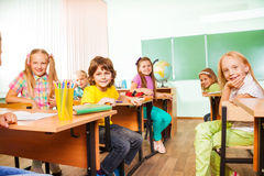 Table rows with boys and girls looking straight Stock Photography
