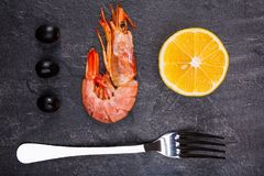On the table is royal prawn, slice of lemon, a few olives and a fork. On the table is one royal prawn, a slice of lemon, a few black olives and a fork. View Stock Photo