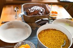 Table with saffron rice in pot, plates, baked chicken and peach compote. Lunch or dinner table with saffron rice in pot,two  plates, baked chicken and pech Royalty Free Stock Image