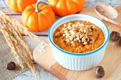 Table scene with bowl of autumn pumpkin oatmeal Royalty Free Stock Photography