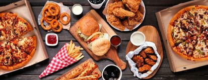 Free Table Scene Of Assorted Take Out Or Delivery Foods, Top Down View On A Dark Wood Banner Stock Images - 184617174