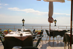 Table by the Sea. Restaurant tables with a perfect sea view stock photo