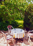 Table and seats in the garden under cherry tree Royalty Free Stock Photography