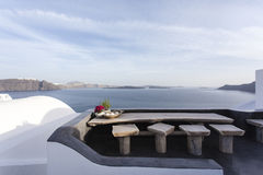 Table with seats and the view at the sea and volcano, Oia, Santorini (Thera) - The Cyclades - Greece Royalty Free Stock Photos