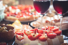 Table served with appetizers in the form of canapes and glasses of wine in the restaurant. Table served with appetizers in the form of canapés with cheese and stock photo