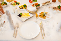 Table served with different food and flatware Stock Image