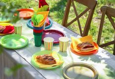 Table served with disposable tableware. In garden Royalty Free Stock Image