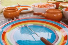 Table served for outdoor picnic with colored plate in the foreground. Table served for outdoor picnic with colored plate and skewer in the foreground. Toned Stock Photo
