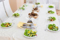 Salad plates for 10 persons. Table served with salad plates for 10 persons with selective focus Stock Photo