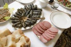 Table servie avec des feuilles de raisin bourré et un casse-croûte Photo stock