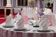 Table servie avec des serviettes, des cartes et des verres d'intérieur Photographie stock