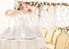 Table servie pour le dîner d'événement avec des couverts et des verres, décorée des compositions florales dans des vases Photos libres de droits