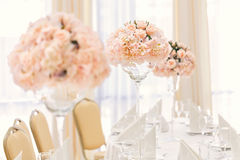 Table servie pour le dîner d'événement avec des couverts et des verres, décorée des compositions florales dans des vases Photographie stock