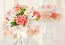 Table servie pour le dîner d'événement, décorée des compositions florales dans des vases aux nuances roses et de corail Bouquet d Image libre de droits