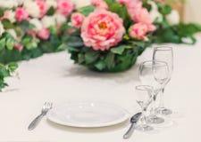 Table servie pour une personne avec un ensemble de verres, décoré des fleurs naturelles Dîner d'événement Photos libres de droits