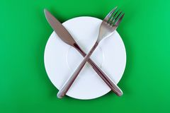 Table serving-dishware on green backdrop. Royalty Free Stock Photo